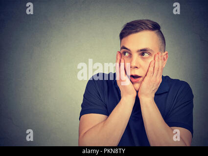 Young man holding hands on cheeks in great expression of fear looking away on gray background - Stock Photo