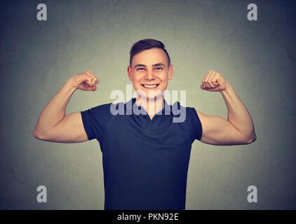 Happy fit young man showing biceps and smiling at camera excited with success - Stock Photo