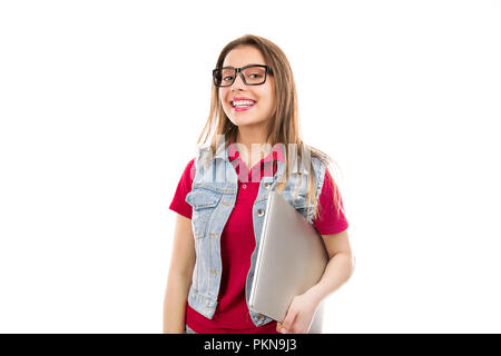 Pretty young woman in eyeglasses holding laptop and smiling at camera isolated on white background - Stock Photo