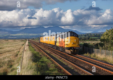 A Colas Railfreight class 37 locomotive passing Dunnerholme on the Cumbrian coast line with a Network rail infrastructure monitoring train (PLPR) - Stock Photo