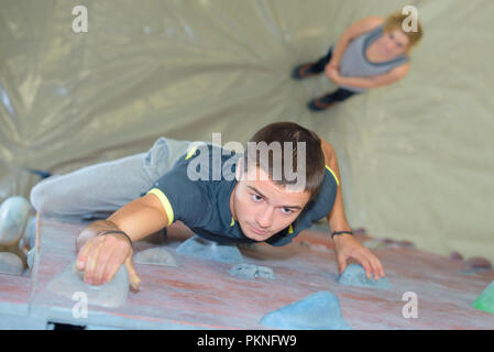 Man on indoor climbing wall - Stock Photo