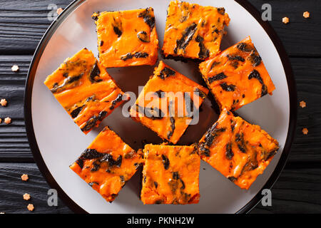Festive Halloween delicious sweet dark brownie cake decorated with orange pumpkin cream close-up on a plate. Horizontal top view from above - Stock Photo
