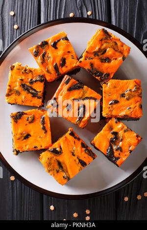 Festive Halloween delicious sweet dark brownie cake decorated with orange pumpkin cream close-up on a plate. Vertical top view from above - Stock Photo