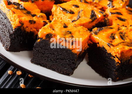 Festive Halloween delicious sweet dark brownie cake decorated with orange pumpkin cream close-up on a plate. horizontal - Stock Photo