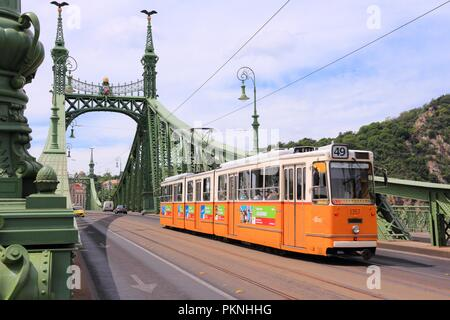 BUDAPEST, HUNGARY - JUNE 20, 2014: People ride orange tram in Budapest. It is part of BKK public transport system which serves 1.4 billion annual ride - Stock Photo