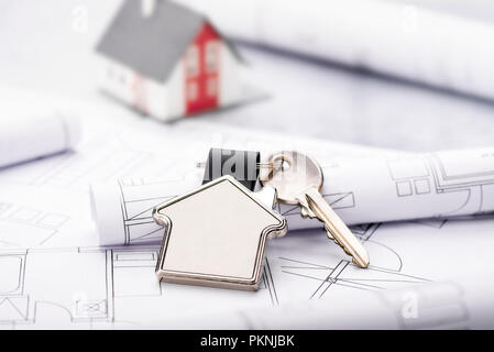 Blueprints and house as a key ring with architectural model in the background - Stock Photo