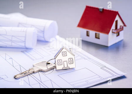 Blueprints and house as a keychain with architectural model - Stock Photo