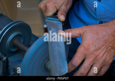 Man grinding on abrasive cutting and knife-sharpening stones - Stock Photo