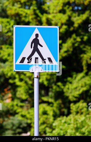 Blue warning road sign with pedestrian symbol - Stock Photo