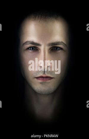 Contrasting male portrait on black background. Light and shadow on the man's face. Stylish, brutal man, art photo. Silhouette face serious macho, expr - Stock Photo