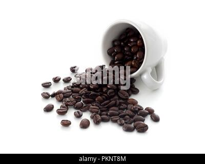 Coffee beans spilling from cup. - Stock Photo