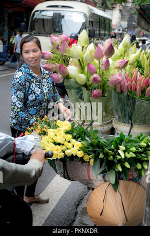 The street vendor sells flowers on the bicycle in the morning in Hanoi Old Quarter, Vietnam. - Stock Photo