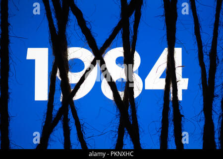 Smartphone in the dark, tightly wrapped and tied with coarse jute rope bondage with glowing blue screen with white text '1984'. Concept of censorship  - Stock Photo
