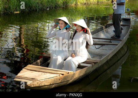 Two Vietnamese girls are gentle in culture traditional white long dress on the boat at Hue city, Vietnam - Stock Photo