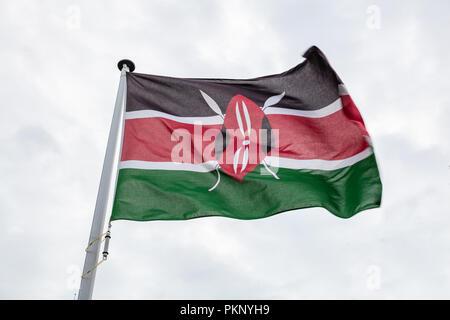 Kenya flag on a pole waving on cloudy sky background - Stock Photo