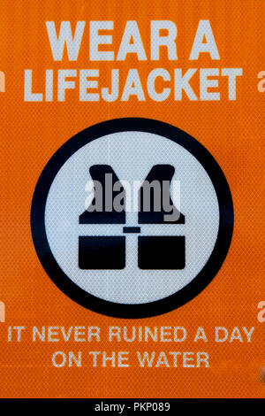 Wear a Jacket signage warning boat crews fo safety on the water. - Stock Photo