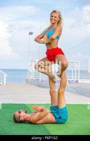 young couple woman and men on field doing fitness yoga exercise together. Acroyoga element for strength and balance - Stock Photo