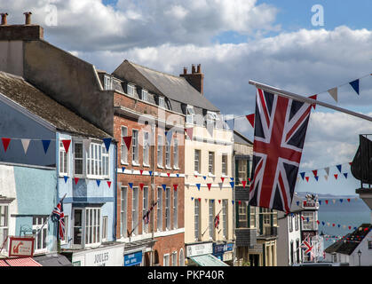 Flags and bunting hanging over Broad Street, Lyme Regis, Dorset, England, UK. - Stock Photo