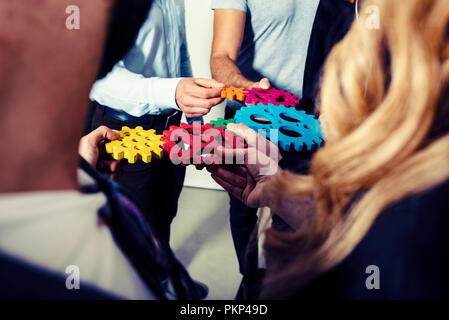 Business team connect pieces of gears. Teamwork, partnership and integration concept - Stock Photo