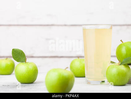 Glass of fresh organic apple juice with granny smith and british bramley apples in box on wooden background. - Stock Photo