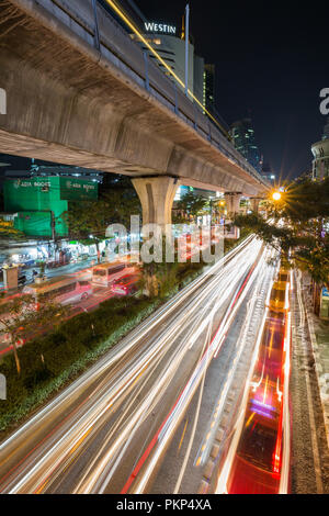 Scenic view of elevated skytrain track and traffic's light trails on Sukhumvit Road in downtown Bangkok, Thailand, at night. - Stock Photo
