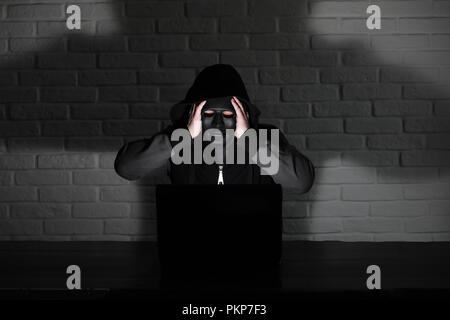 Hacker in black mask and hood at the table - Stock Photo