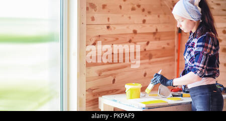 Woman with brush in a wooden house - Stock Photo