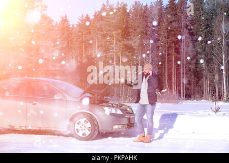 Man stands outdoor near broken car - Stock Photo