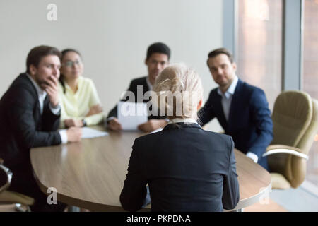 Woman passing job interview at office, interviewers on backgroun - Stock Photo