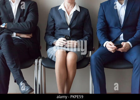 Business people sitting in chairs in queue waiting job interview - Stock Photo