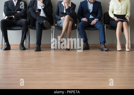 Businesspeople legs sitting in chair in queue wait job interview - Stock Photo