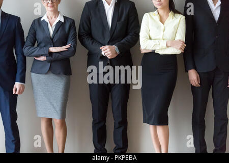 Young and mature business people standing together in row - Stock Photo
