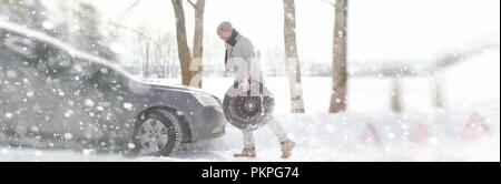 A man near a broken car on a winter day - Stock Photo