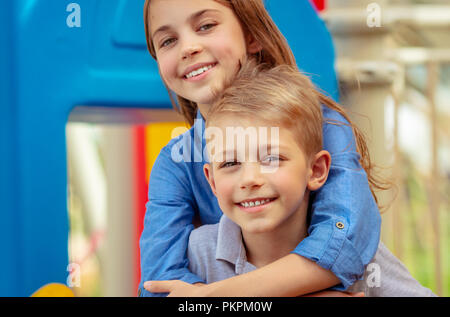 Closeup portrait of a cute little kids with pleasure playing with each other on the playground, active summer holidays, brother and sister enjoying sp - Stock Photo