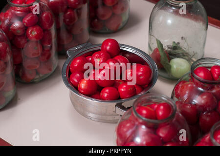 tomatoes prepared for canning houses in glass jars - Stock Photo