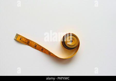 Yellow fiberglass tape measure on a white background. - Stock Photo
