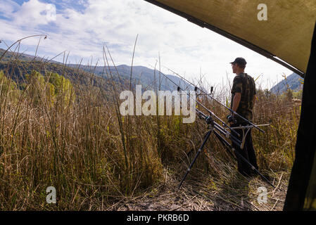 Fishing adventures, carp fishing in autumn. Fisherman with camouflage shirt is waiting on the shore of a lake, hidden behind the reeds - Stock Photo