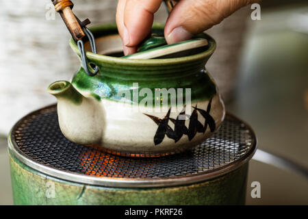 Sushi rolls, sashimi set, miso soup and teapot, on dark wooden table, Japanese food, top view. - Stock Photo