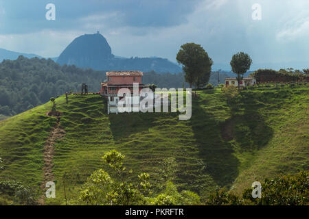 Colombian house on the top of a green hill with the Rock of Guatape in the background - Stock Photo