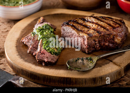 A delicious medium rare fire grilled argentina style steak with chimichurri verde sauce. - Stock Photo