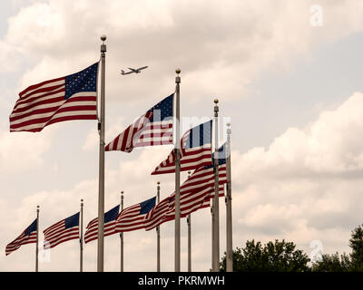 WASHINGTON, USA - AUGUST 25, 2017: Several USA flags and an airplane flying above - Stock Photo