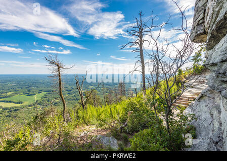 Looking out toward the horizon & cloudy sky from a hiking trail along Pilot Mountain in North Carolina, USA. - Stock Photo