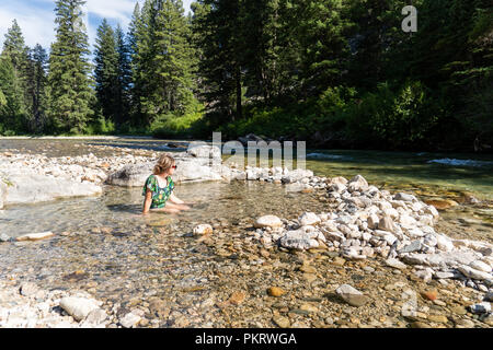 Woman sits and enjoys a dip in the hot springs in Grandjean Idaho in Sawtooth Mountains