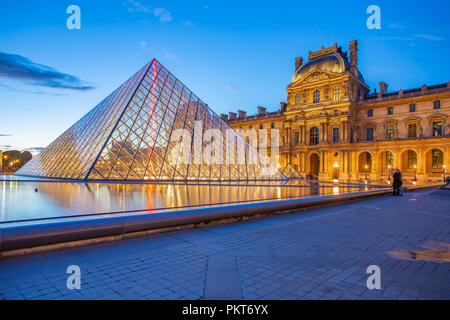 Paris, France - May 13, 2014: Pyramid Glass with view of Louvre Museum at night in Paris. - Stock Photo