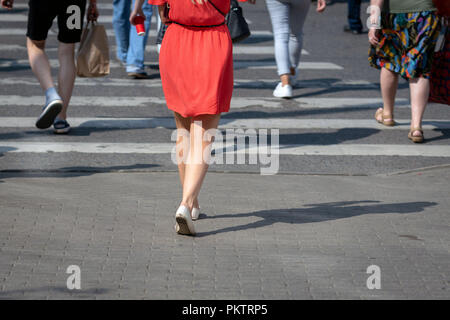 On a sunny day, pedestrians cross the street through a pedestrian crossing. There are pedestrian shadows on the street. View from the back. - Stock Photo