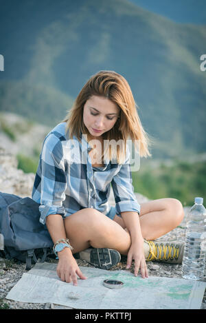 Young woman reading map in mountain - Stock Photo