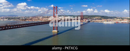 Ponte 25 de Abril Bridge in Lisbon, Portugal. Connects the cities of Lisbon and Almada crossing the Tagus River. View from Almada with Lisbon across t - Stock Photo