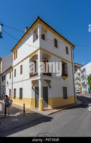 Spain, Ronda - 21 June 2017: Person walking ON ROAD BY BUILDINGS AGAINST SKY IN CITY - Stock Photo