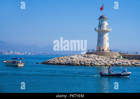 Boats at the lighthouse, harbor entrance of Alanya, seaside resort on the Turkish Riviera, Turkey - Stock Photo