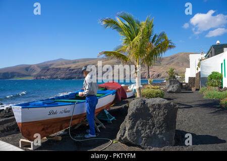 Old fisherman grooms his boat in the small fishing village Playa Quemada, Lanzarote, Canary Islands, Spain - Stock Photo